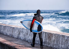 Surfer walking into water in winter on pier Stock Images