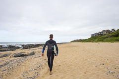 Surfer walks along beach with surfboard Royalty Free Stock Images