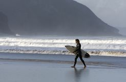 Surfer walks away from waves with surfboard. A surfer walks away from the water with his surboard on Porthtowan beach, Cornwall, UK with sloping cliffs in the stock photo
