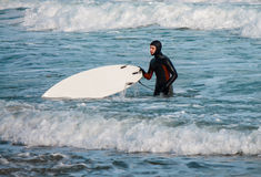 Surfer walks from water with surfboard w Stock Photo