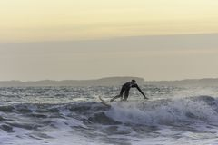 Surfer wat betreft de golf terwijl het vangen van saldo tijdens avondbranding in ruwe overzees royalty-vrije stock afbeeldingen