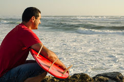 A surfer watching the waves. Sitting down with his arms around his surfboard Royalty Free Stock Photography