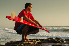 Surfer watching the waves. A surfer watching the waves sitting down with his arms around his surfboard Stock Image