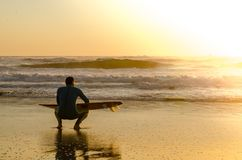 Surfer watching the waves. A surfer watching the waves at sunset in Portugal royalty free stock photos