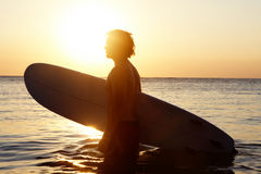 Surfer in water. Portrait of young man in water with windsurf board at sunset Stock Image