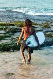 Surfer in the water. The surfer is holding a surfboard on the Indian Ocean shore Stock Image