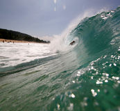 Surfer in the wave. A surfer rides a wave along the shore Stock Photos