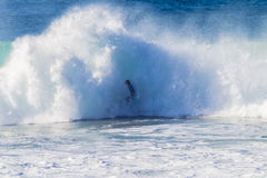 Surfer Wave Crashing. Surfer unidentified just about to be engulfed, swallowed,drowned or covered by the large ocean wave white water that has just exploded Royalty Free Stock Image