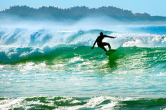 Surfer on a wave. Silhouette of a surfer riding a wave in the ocean Stock Photo