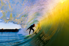 Surfer on Wave at Sunset. Surfer on Amazing Wave at Sunset, in the Barrel, Epic Tube Royalty Free Stock Images