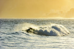 Surfer in the wave at sunset Stock Photography