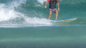 Surfer on the wave. The surfer leaves the pipe. Waves on the island Taken from the water. The surfer catches the wave royalty free stock photo