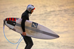 Surfer wearing gath surf helmet and wetsuit at sunrise. CAPE SOLANDER, AUSTRALIA - AUGUST 27, 2015; Surfer wearing a gath surf helmet and wetsuit and carrying a Stock Photography