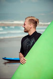 Surfer wearing wetsuit standing on the beach with a surfing board.  Royalty Free Stock Photography