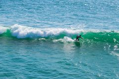 Surfer in a wet suit balancing on his surf board while riding a small wave in the blue green Pacific Ocean royalty free stock images