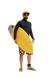 Surfer in a wetsuit holding a surfboard. Full length portrait of a surfer in a wetsuit holding a surfboard isolated on white background Stock Image