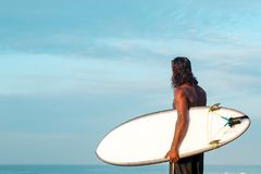 Surfer with a white surfboard. The surfer is holding a surfboard on the Indian Ocean shore Royalty Free Stock Images