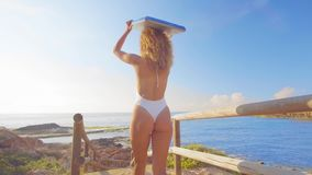 Surfer woman on beach vacation travel going surfing walking with surfboard at sunset on tropical beach. Surfing girl at stock video footage