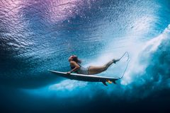 Surfer woman dive underwater. Surfgirl dive under wave. Surfer woman dive underwater. Surfgirl dive under big wave royalty free stock images