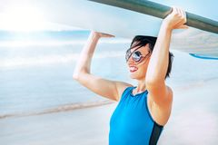 Surfer woman with longboard going into ocean waves. Active vacation concept image stock photo