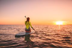 Surfer woman on stand up paddle board at quiet sea with warm sunset colors. Relaxing on ocean stock photo