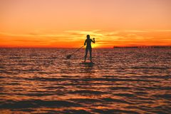 Surfer woman stand up paddle boarding at dusk on a flat warm quiet sea with beautiful sunset colors. Surfer woman stand up paddle boarding at dusk on a flat warm Royalty Free Stock Photography