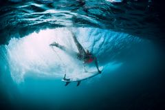 Surfer woman with surfboard dive underwater with under big ocean wave. royalty free stock image