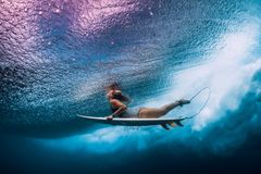 Surfer woman with surfboard dive underwater with under ocean waves. Surfer woman with surfboard dive underwater with under ocean wave stock photography