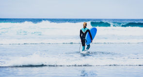 Surfer woman with surfboard is walking and watching the waves. Royalty Free Stock Photo