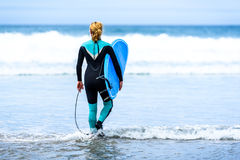 Surfer woman with surfboard is walking and watching the waves. Stock Photos