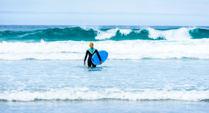 Surfer woman with surfboard is walking and watching the waves. Stock Photo
