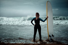 Surfer woman wearing wetsuit standing on the beach with a surfboard.  Stock Photo