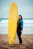 Surferfrau tragender Wetsuit, der auf dem Strand mit einem Surfbrett steht Stockbilder
