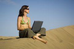 Surfergirl on laptop. Girl working on her laptop in the dunes in Gran Canaria royalty free stock images