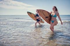 Surfermädchen, das mit Brett geht Surfer-Mädchen Schönes junges Wom stockbilder