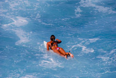 Surfermädchen, das schaufelt, um eine Welle abzufangen Stockfotos