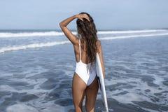 Surfermädchen in einem weißen Badeanzug geht zum blauen Ozean, mit einem weißen Surfbrett Stockbilder