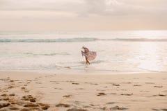 Surfermädchen mit Surfbrett auf einem Strand bei Sonnenuntergang stockbilder