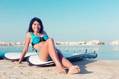 Surfermädchen nah an Wasser auf Stadtstrand Lizenzfreie Stockbilder