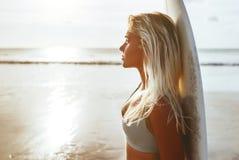 Surferm?dchen, das Ozeanstrandsonnenuntergang betrachtend surft stockbild