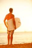 Surfermann auf Strand bei dem Sonnenuntergang, der bodyboard hält Stockfotos