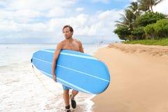 Surfermann gehendes longboard, das auf Maui-Strand surft Stockfotos