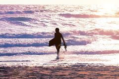 Surfermann am Strand bei Sonnenuntergang lizenzfreie stockbilder