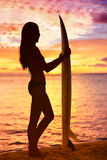 Surfermädchen, das Ozeanstrandsonnenuntergang betrachtend surft Stockfotos