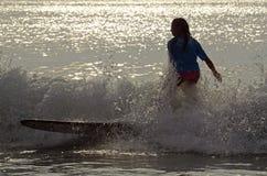 Surfermeisje het Surfen Wedstrijd in Vroeg Ochtendlicht Stock Foto