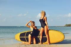 Surfermeisjes die met surfplank op een strand stellen stock foto's