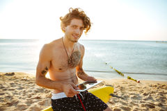 Surfermens die tablet gebruiken terwijl het zitten op de brandingsraad Royalty-vrije Stock Afbeeldingen