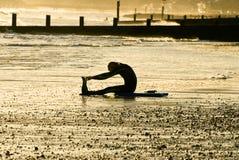 Surferr che allunga sulla spiaggia Immagine Stock