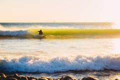 Surferrit op perfecte oceaangolf bij zonsondergang De winter die in zwempak surfen Royalty-vrije Stock Fotografie