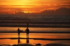 Surfers κάτω από το ηλιοβασίλεμα στοκ φωτογραφία με δικαίωμα ελεύθερης χρήσης